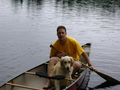 This i a photo of a middle-aged Caucasian man sitting in a canoe with a paddle and a golden retriever sitting in the canoe in front of him on a lake