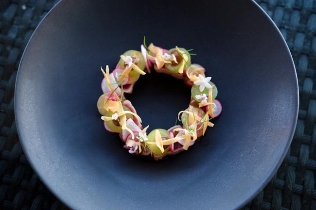 Seared Ahi Tuna with edible flowers on a black plate
