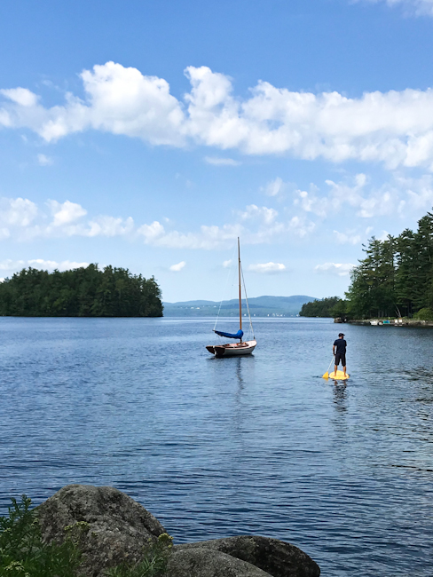 Sailboat and standup paddleboarder on Sebago Lake at Migis Lodge