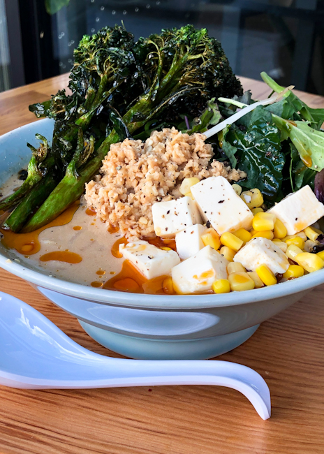 Bowl of vegan ramen with sesame miso broth, broccolini, tofu, bean sprouts, soy meat, baby kale, chili oil