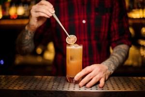 Barman decorating fresh orange lemonade cocktail with a slice of orange