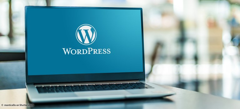 a laptop sitting on the counter, displaying the Wordpress logo