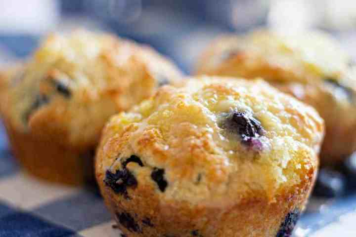 lemon blueberry muffins sitting on blue and white napkin