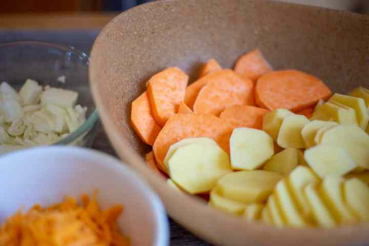 white and sweet potatoes in brown bowl, onions in clear bowl, shredded cheese in bowl