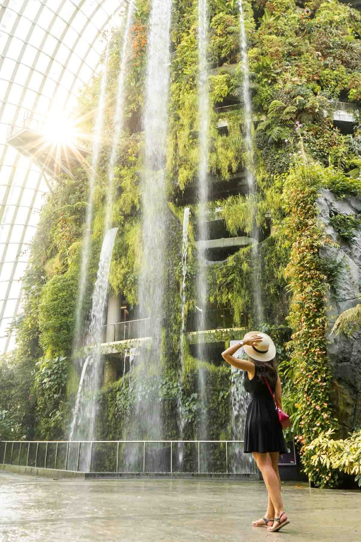 Girl in a black dress standing in fron of an indoor waterfall in the Cloud Forest in Singapore