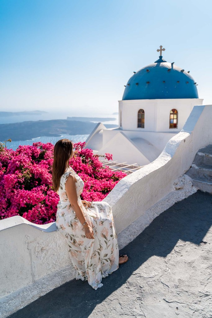 Girl in a floral dress sitting in front of a blue domed church in Imerovigli, Santorini