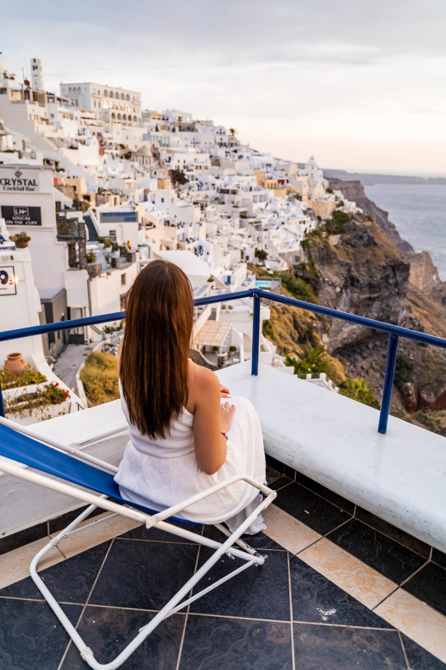 Girl in a white dress sitting at Franco's Bar in Fira, Santorini, watching the view