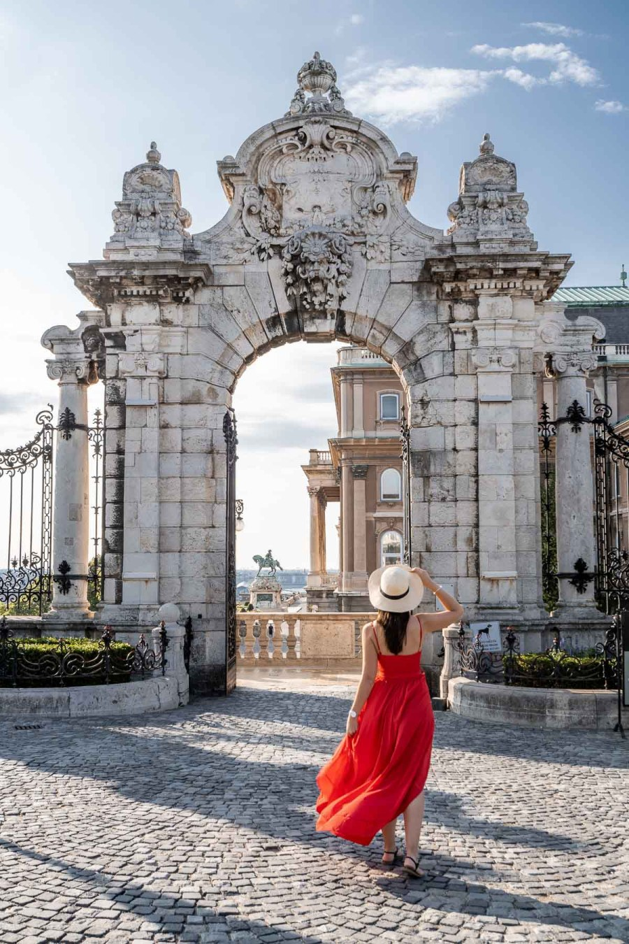 Girl in a red dress and a straw hat standing in front of the Buda Castle