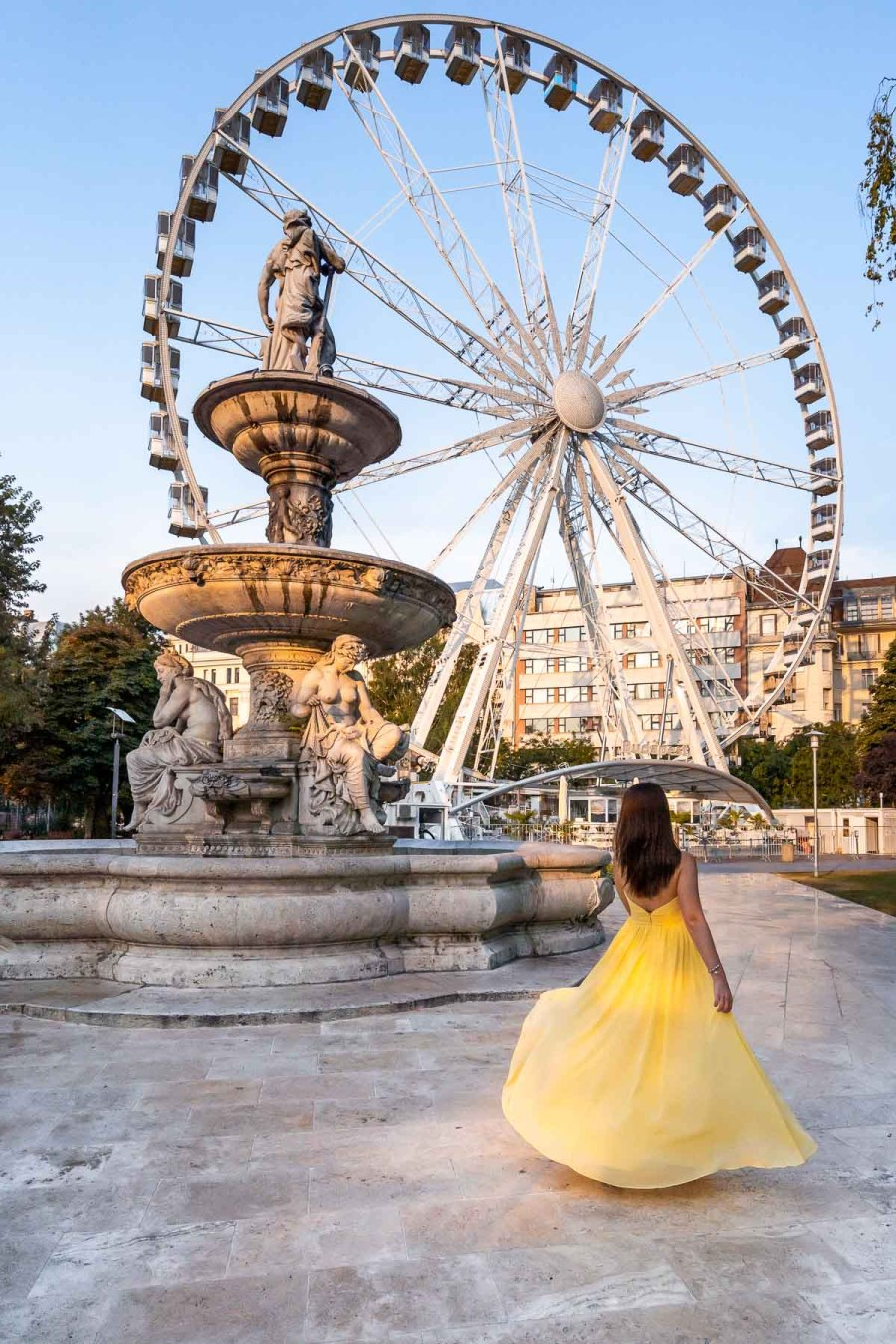 Girl in a yellow dress twirling in front of the Budapest Eye
