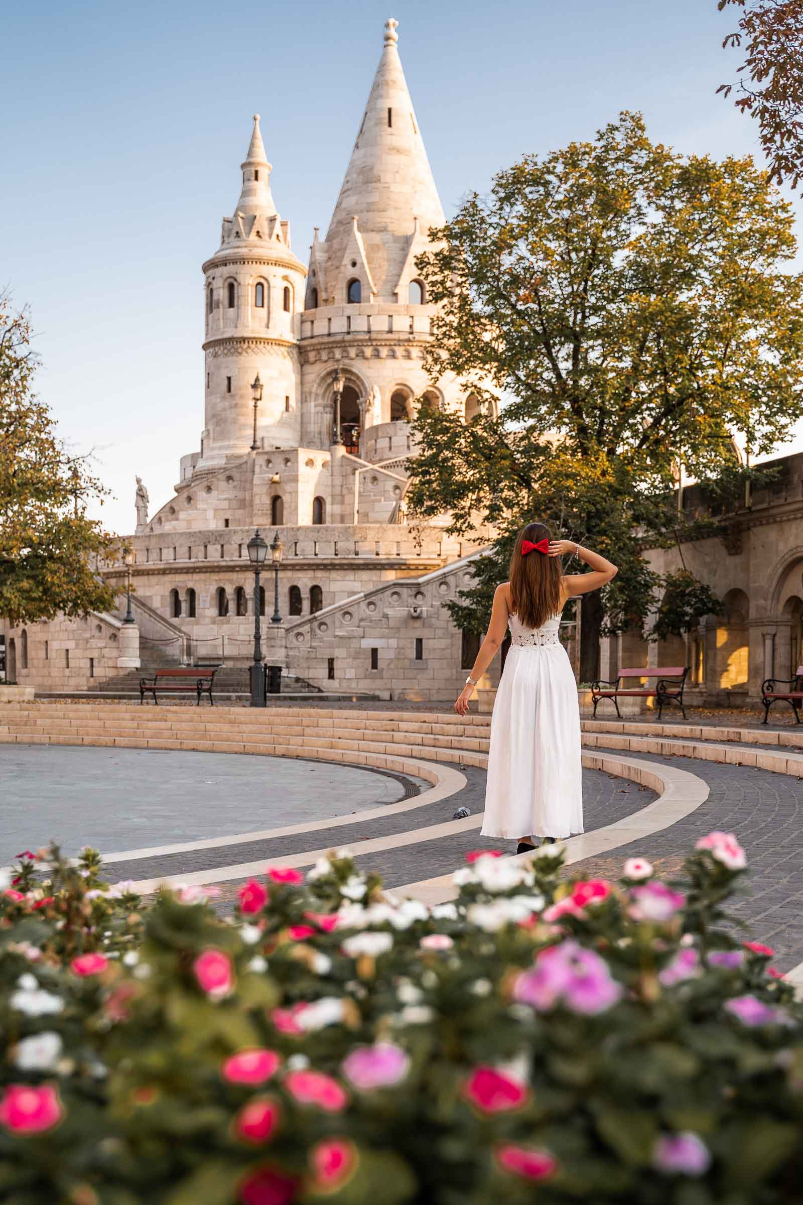 Girl in white dress standing in front of the Fisherman's Bastion in Budapest with colorful flowers in the foreground
