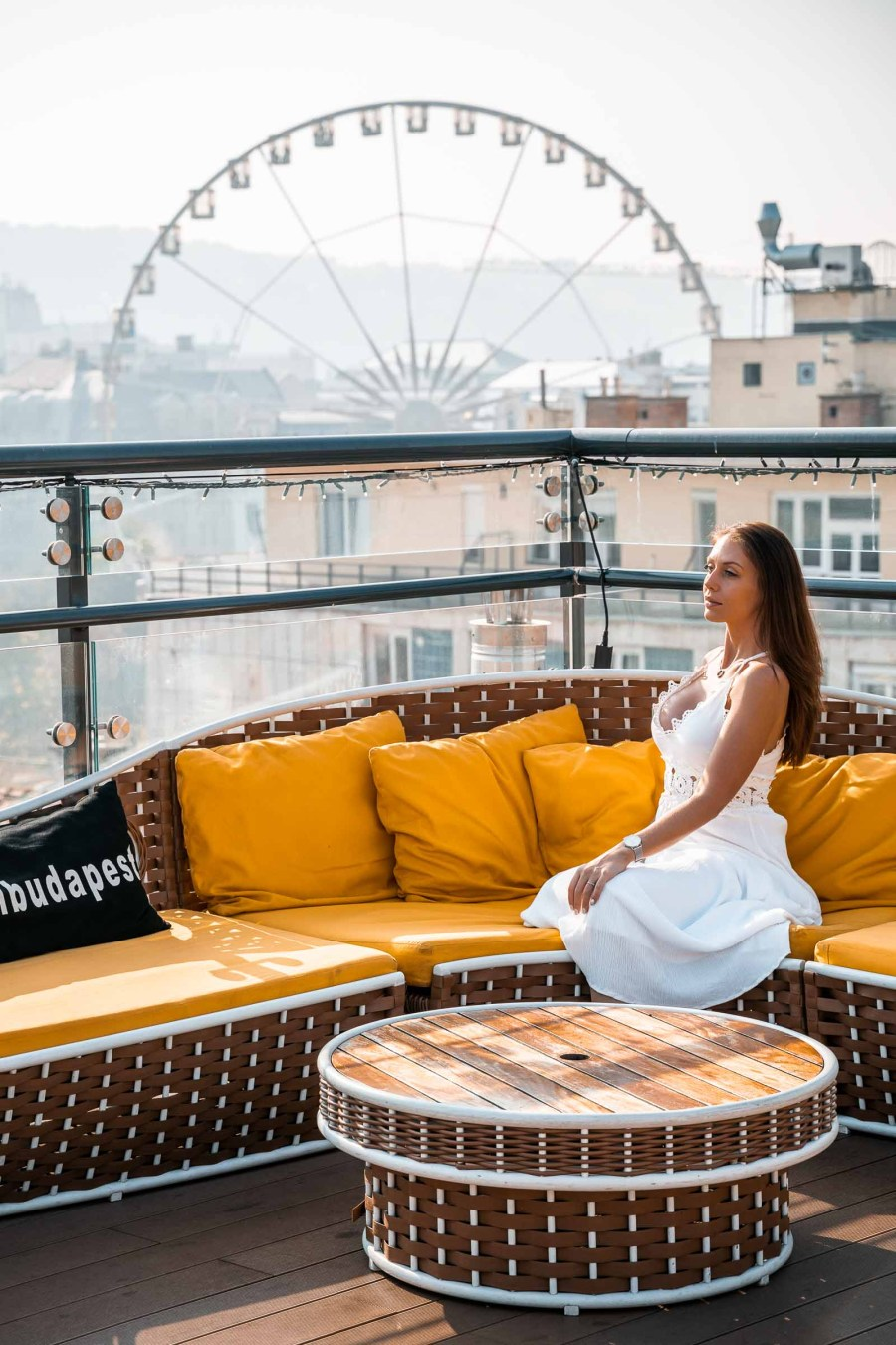 Girl in a white dress sitting in a yellow sofa at the High Note Skybar with the Budapest Eye in the background