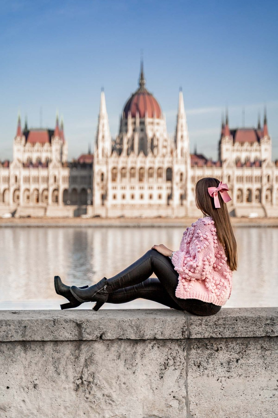 Girl in a pink fluffy cardigan sitting on a wall across the Hungarian Parliament