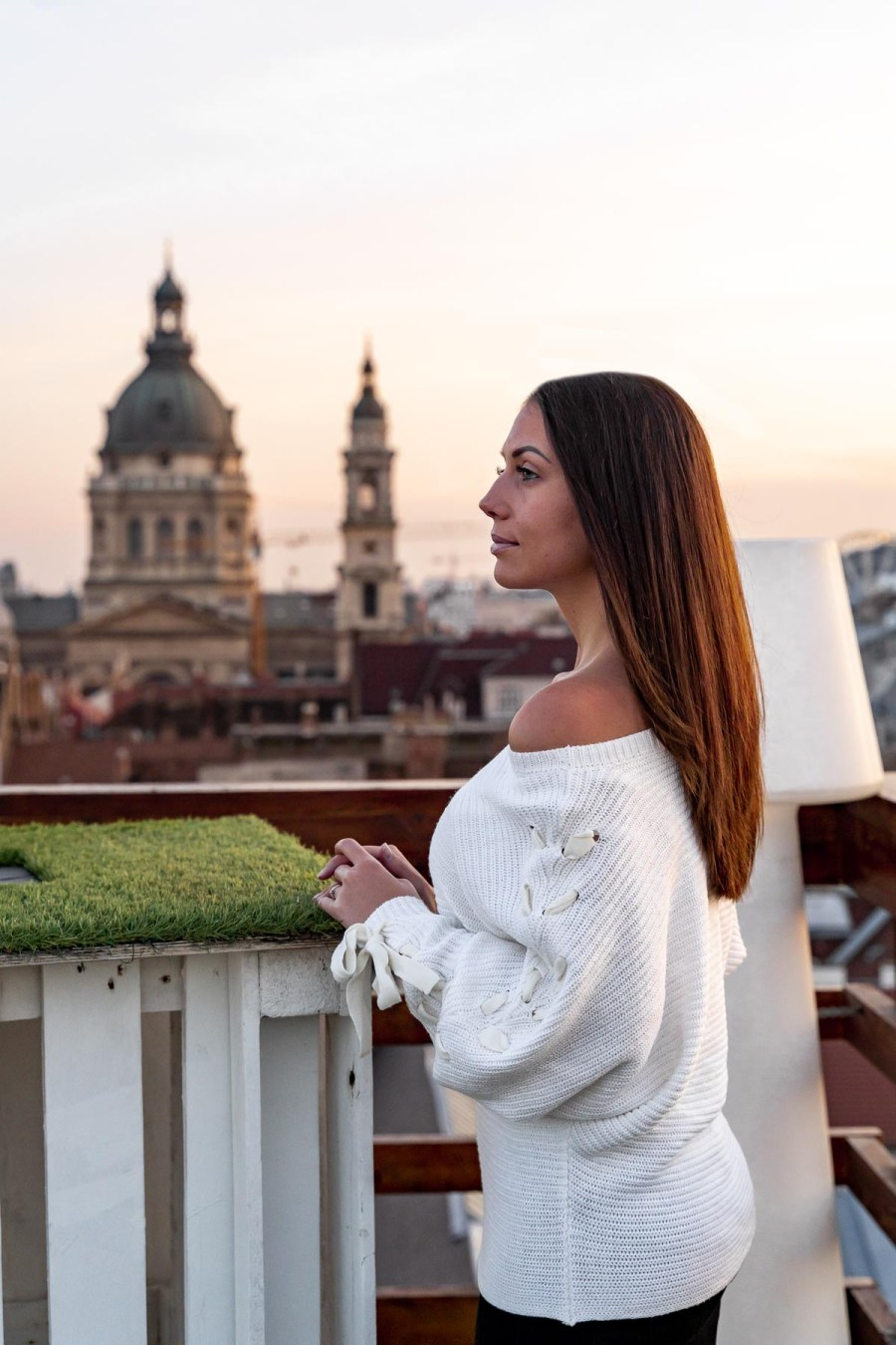 Girl in a white sweater standing at the Intermezzo Roof Terrace, looking at the St. Stephen's Basilica