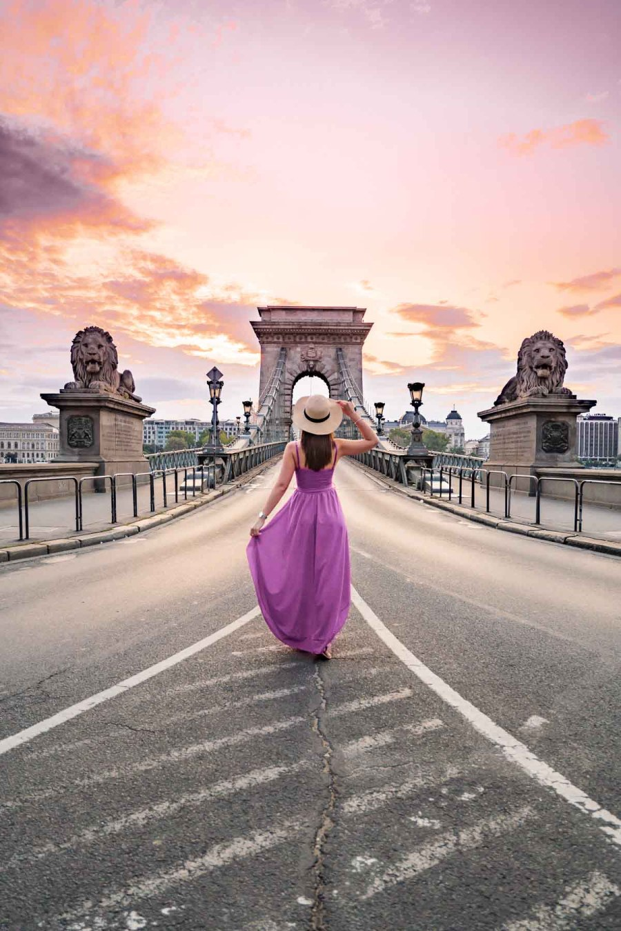 Girl in a purple dress standing in front of the Szechenyi Chain Bridge during sunrise in Budapest