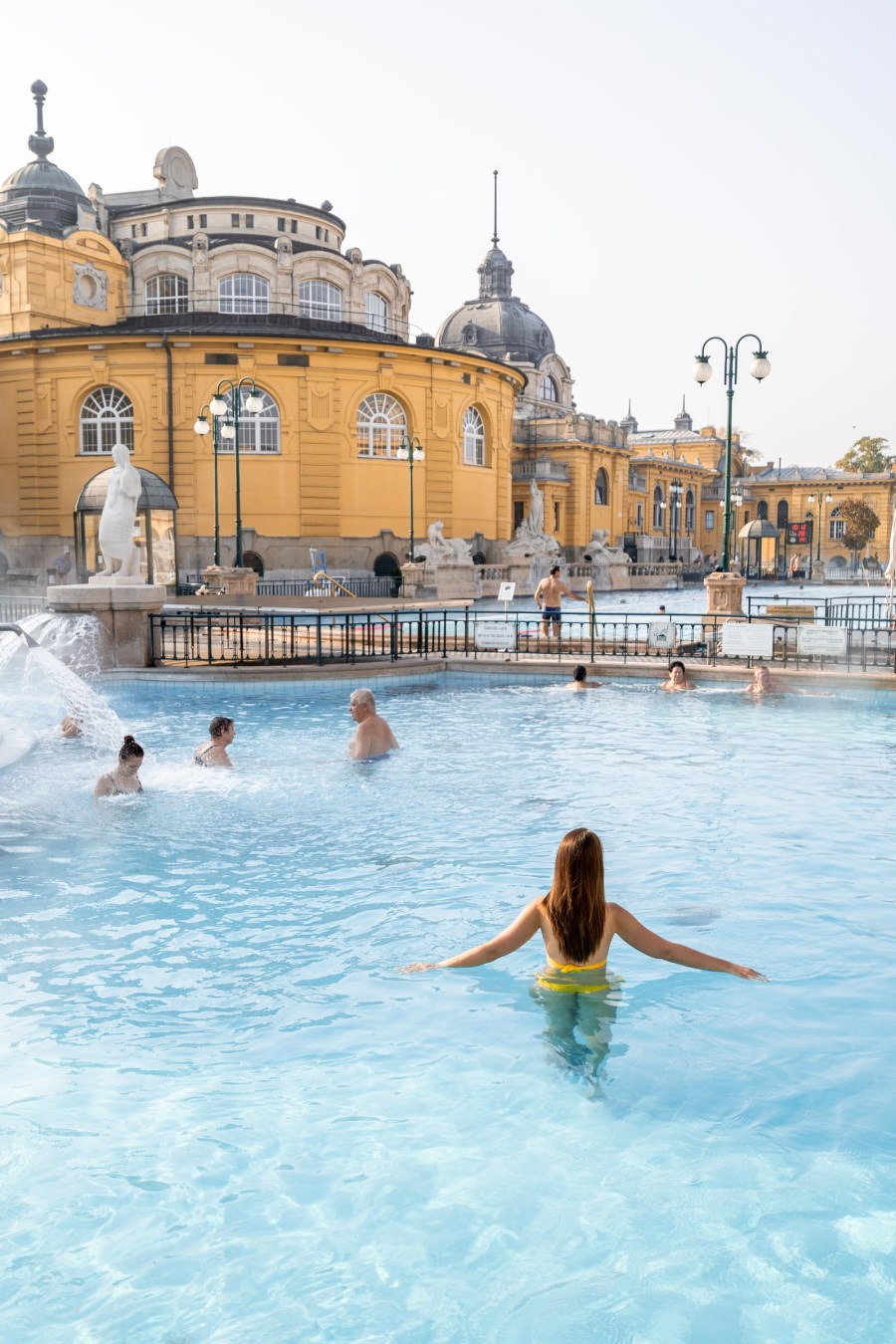 Girl in a yellow bikini standing in the pool in the Széchenyi Thermal Baths in Budapest