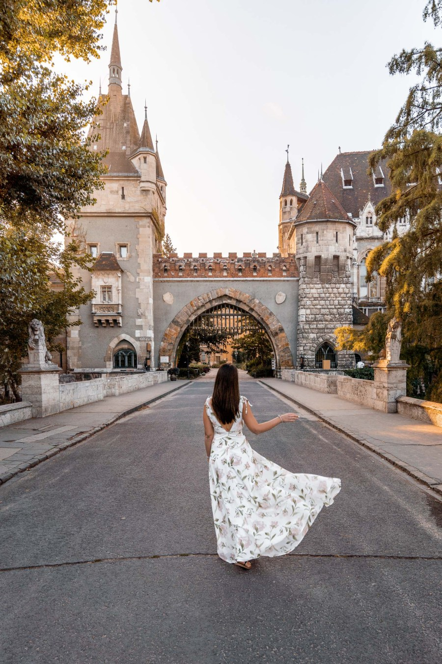 Girl in a white floral dress doing a skirt flip in front of the Vajdahunyad Castle in Budapest