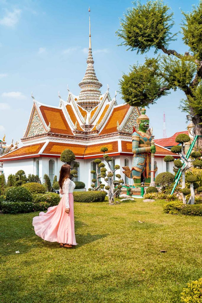 Girl in a pink dress standing in front of the entrance of Wat Arun