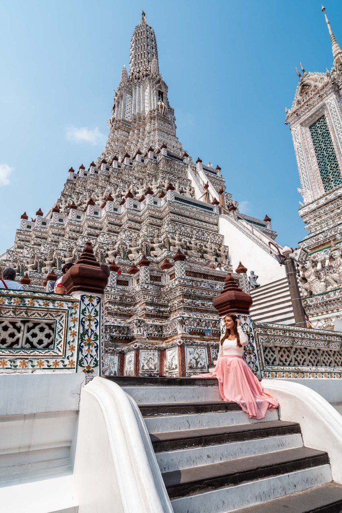 Girl in a pink skirt sitting on the stairs at Wat Arun in Bangkok