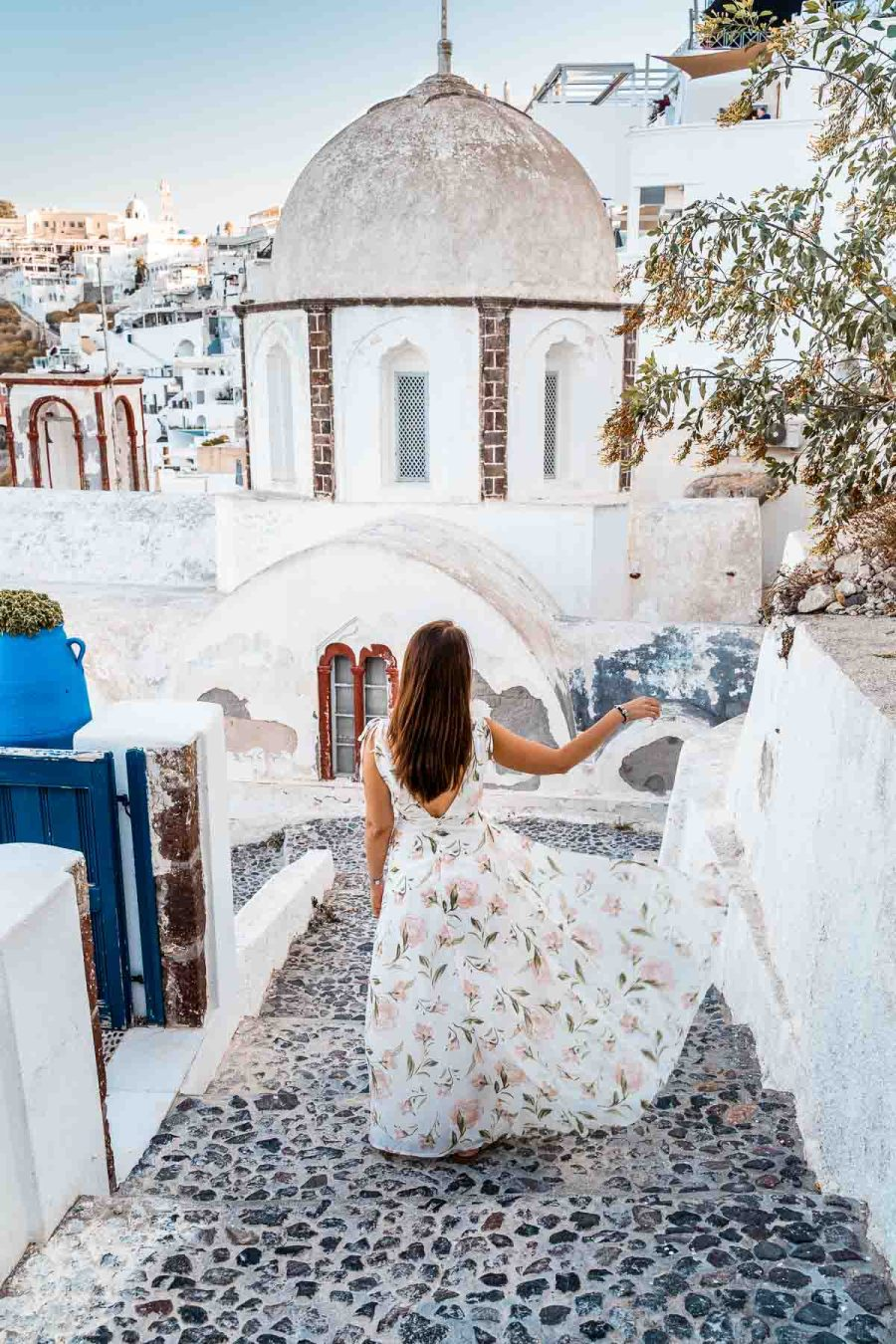 Girl in a floral dress standing in front of the church of St. John in Fira, Santorini
