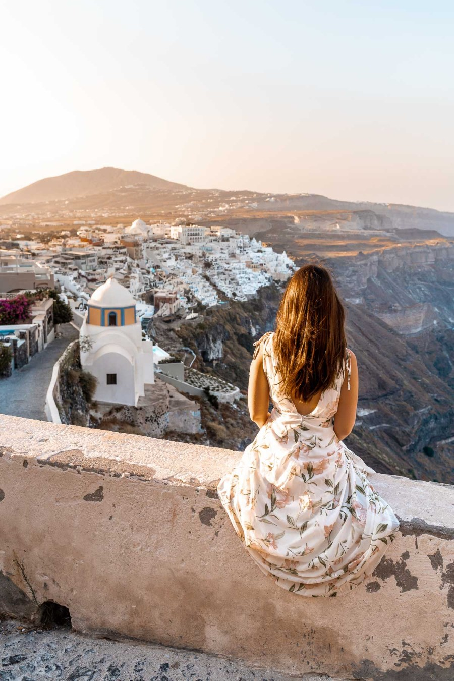 Girl in a floral dress sitting on a wall, watching the sunrise over Fira