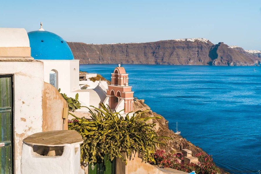 View of the blue sea and a blue domed church in Oia, Santorini