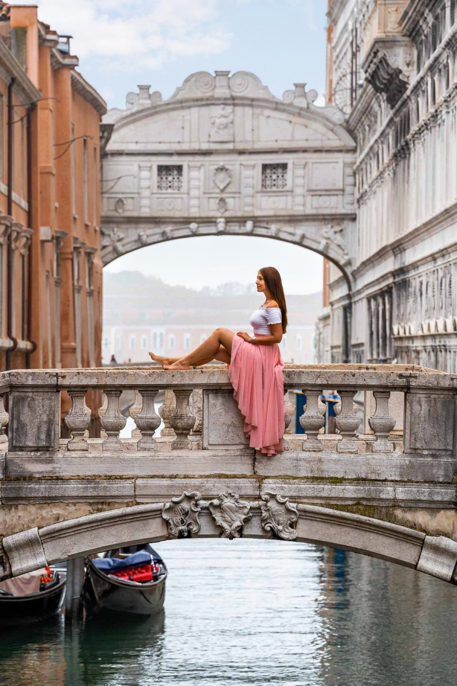 Girl in a pink skirt sitting on a stone bridge in front of the Bridge of Sighs in Venice