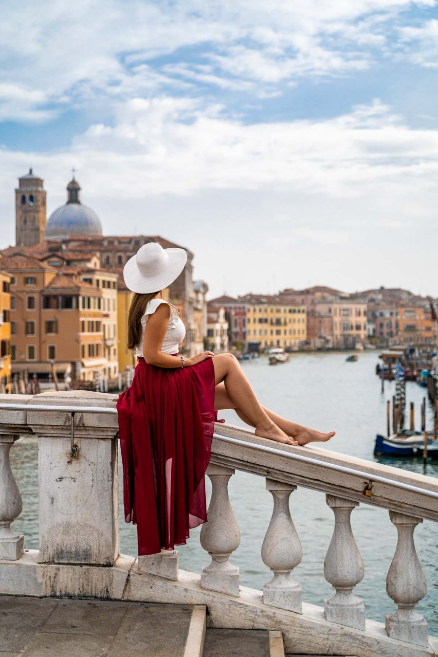Girl in a red skirt sitting on Ponte degli Scalzi in Venice