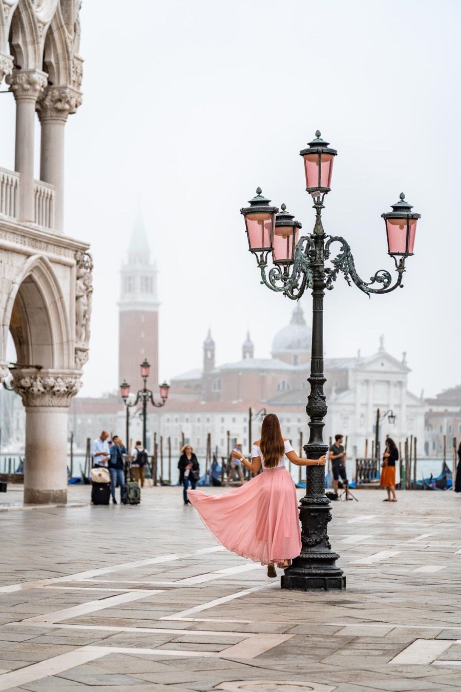 Girl in a pink skirt standing in the middle of Piazza San Marco in Venice, Italy