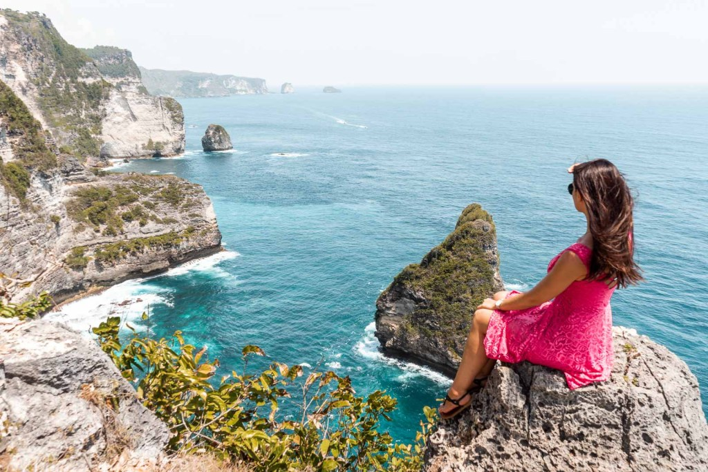 Girl in a pink dress sitting on a cliff, looking at the view at Banah Cliff Point, Nusa Penida