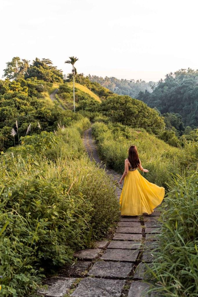 Girl in a yellow skirt walking along the Campuhan Ridge Walk in Ubud, Bali