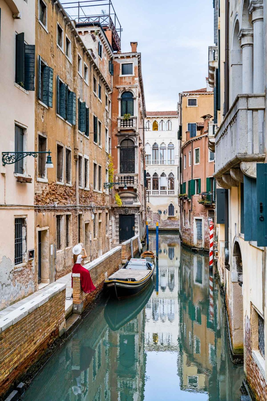 Girl in a red skirt sitting on a wall along the canals at Ponte de La Verona in Venice