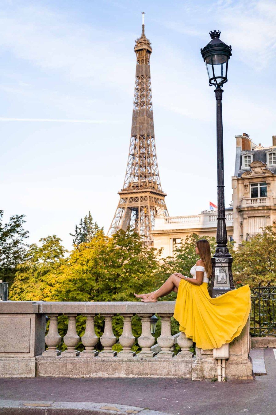Girl in a yellow skirt sitting in front of the Eiffel Tower at Avenue de Camoens, Paris