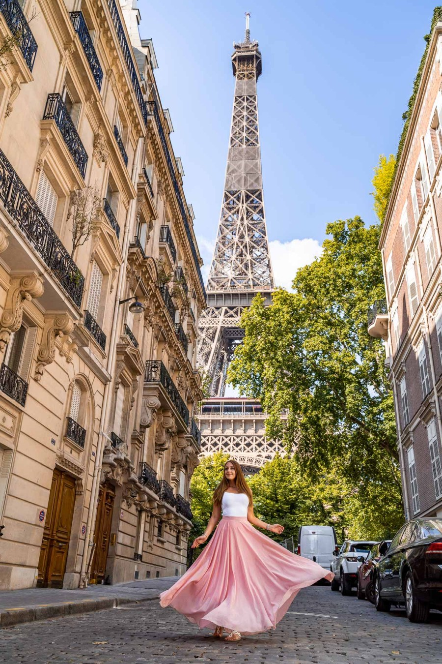 Girl in a pink skirt twirling in front of the Eiffel Tower in Rue de l'Université, one of the most instagrammable places in Paris