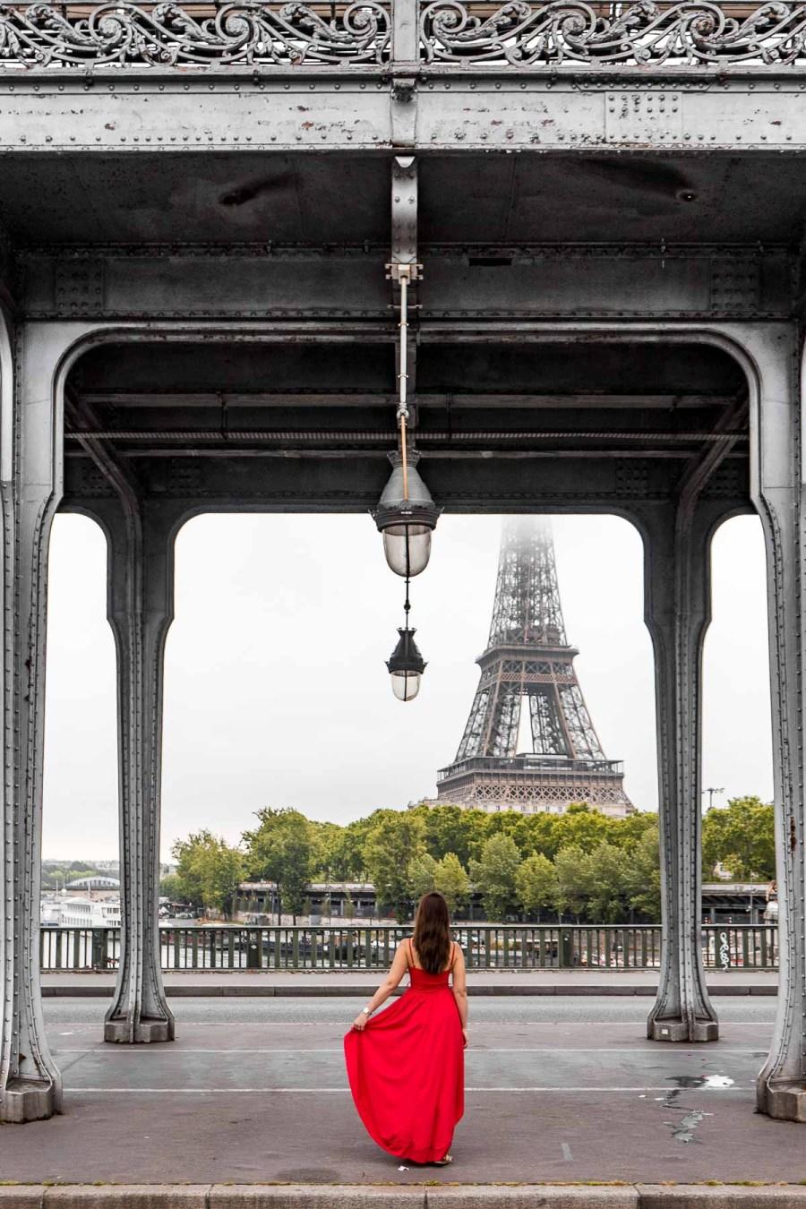 Girl in a red dress standing under Pont de bir-Hakeim, looking at the Eiffel Tower