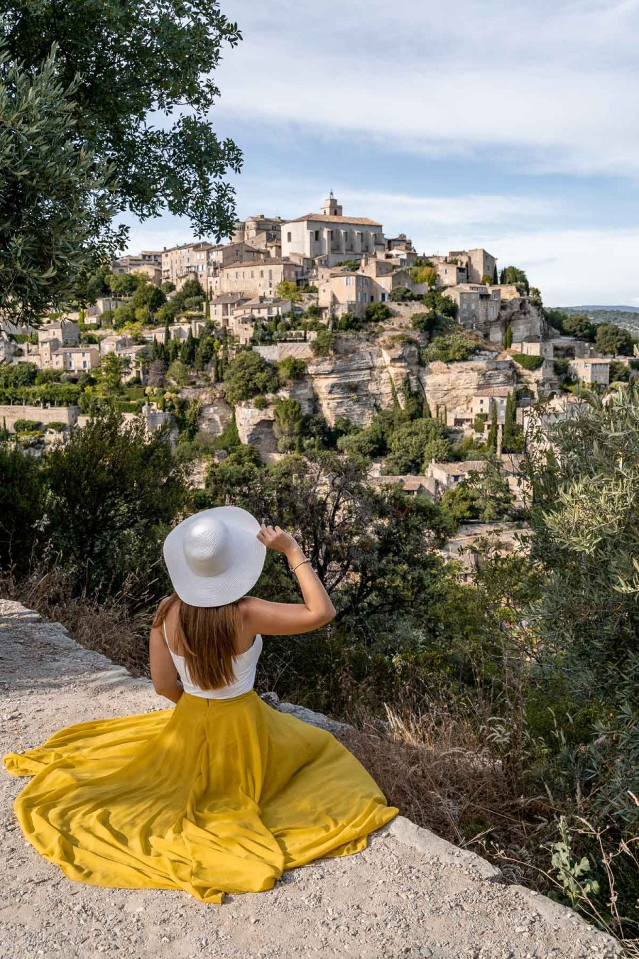 Girl in a yellow skirt sitting at a viewpoint, looking over the beautiful town of Gordes