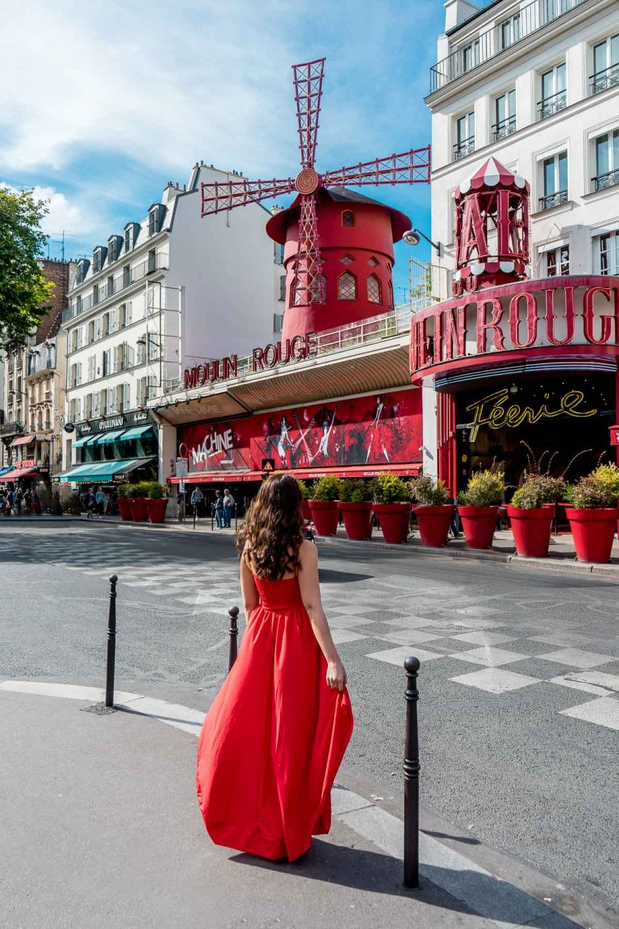 Girl in a red dress standing in front of the Moulin Rouge in Paris