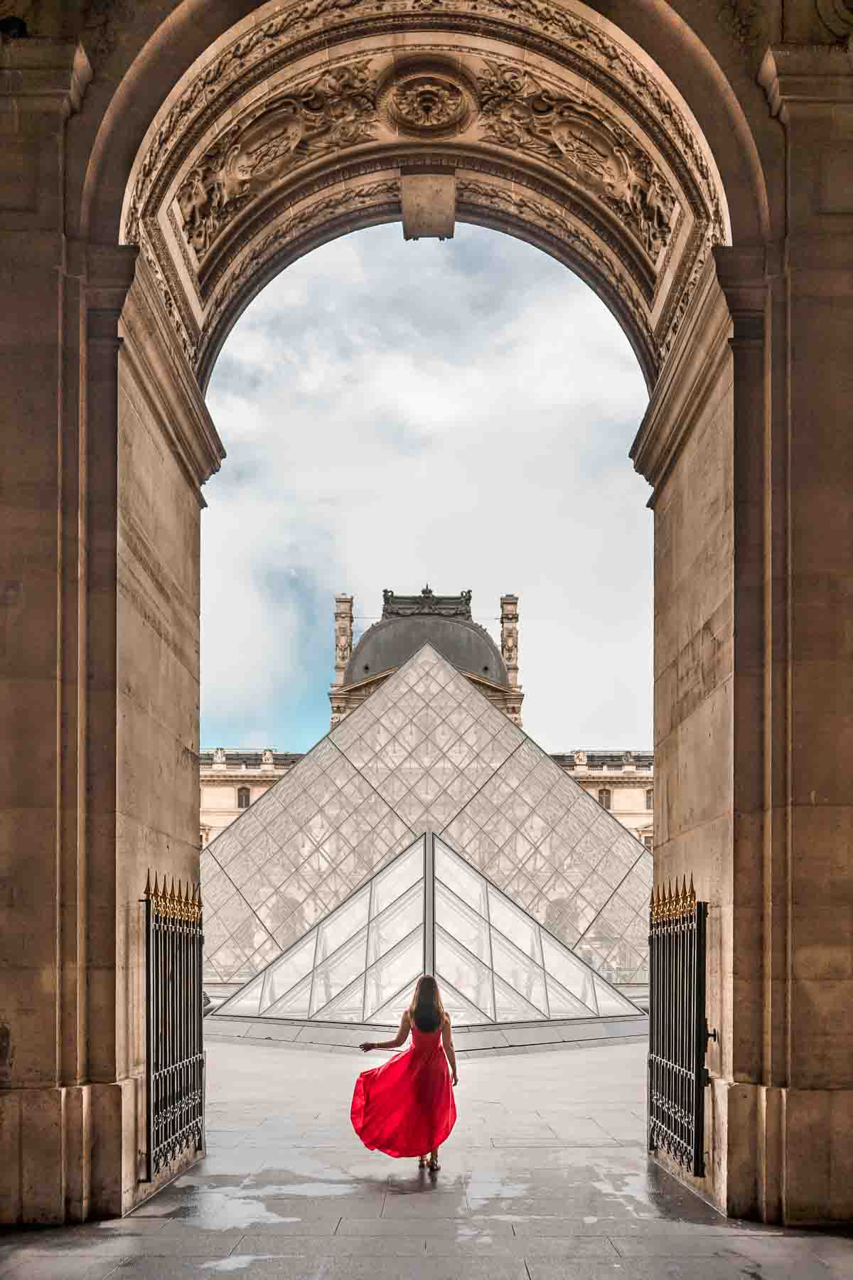 Girl in a red dress standing in front on the Louvre, one of the most instagrammable places in Paris