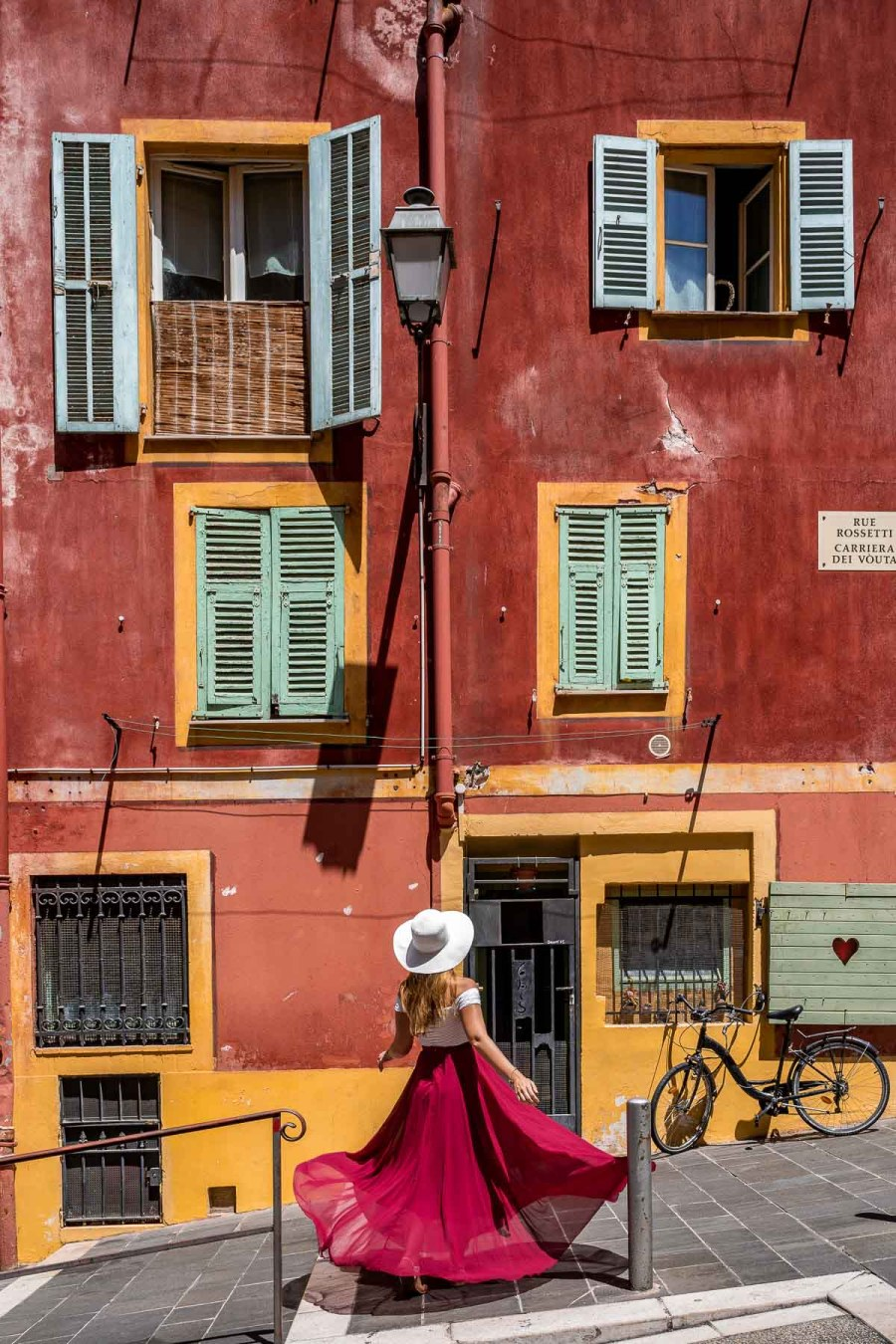 Girl in a red dress twirling in front of a colorful building in Nice, France