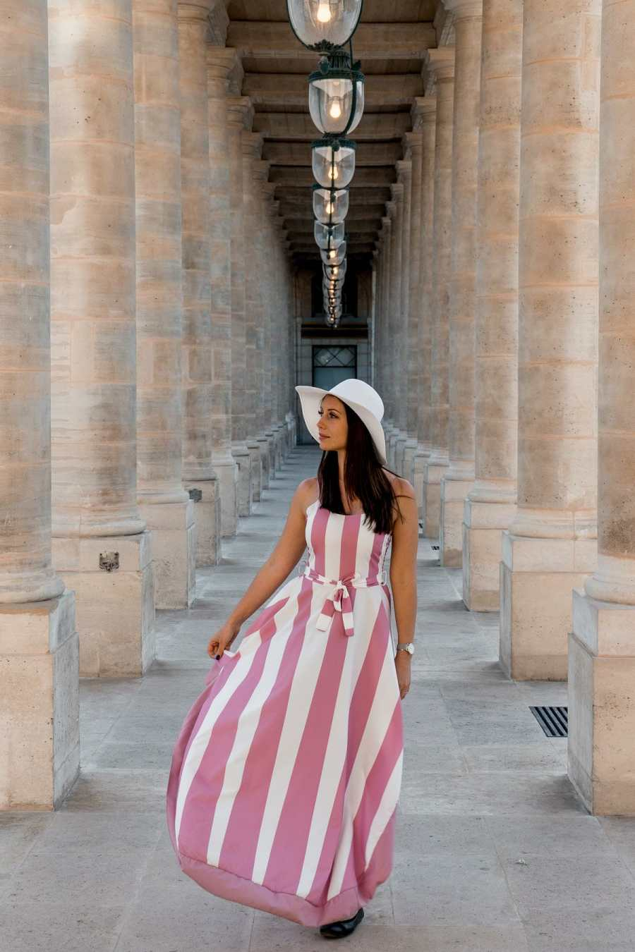 Girl in a pink-white striped dress standing in Palais Royal, one of the best Paris Instagram Spots