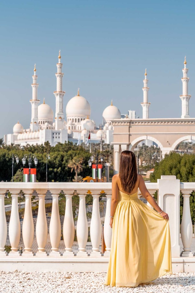 Girl in a yellow dress standing at the Ritz-Carlton Abu Dhabi with the Sheikh Zayed Grand Mosque in the background