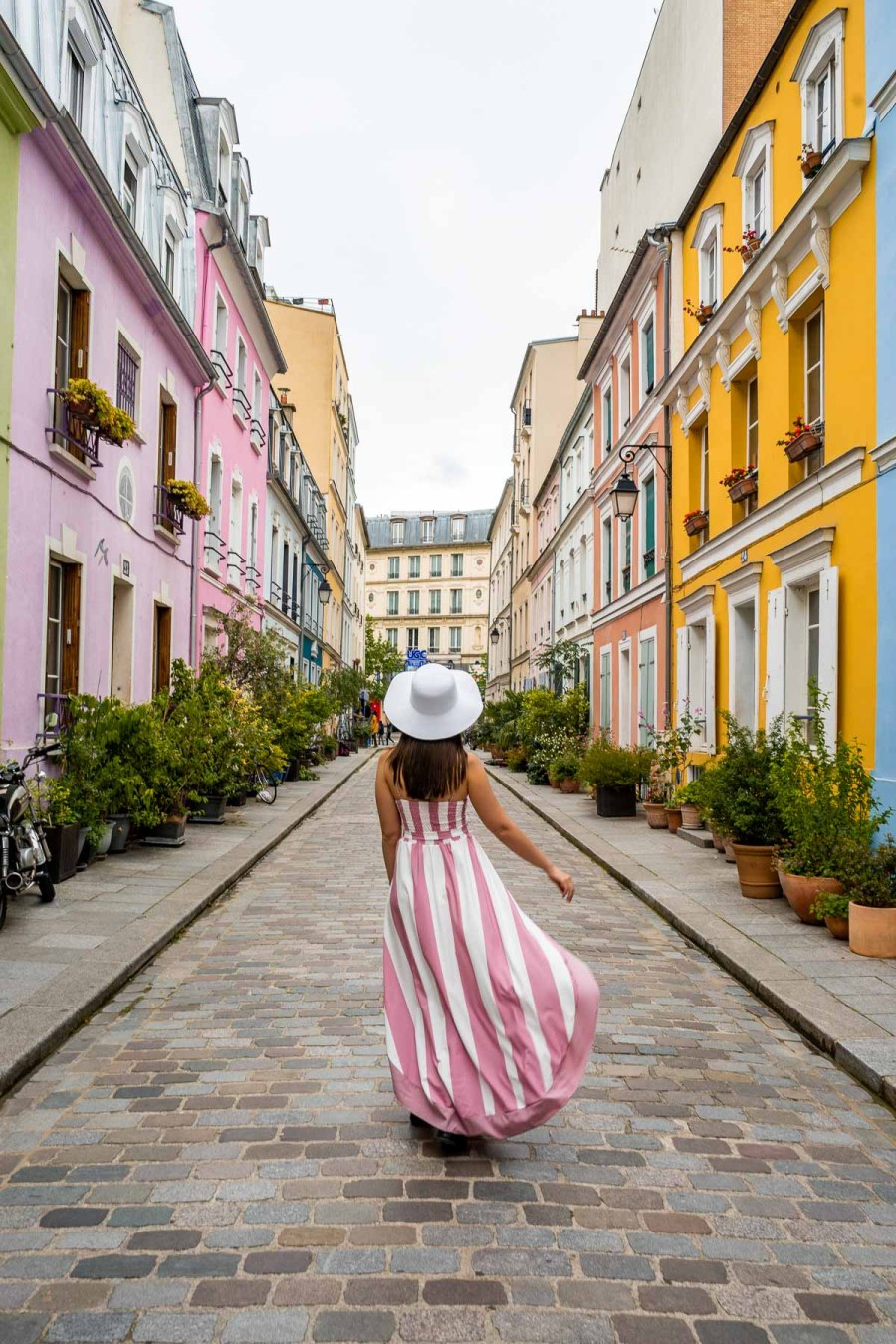 Girl in a pink-white dress twirling in the middle of Rue Crémieux in Paris, France