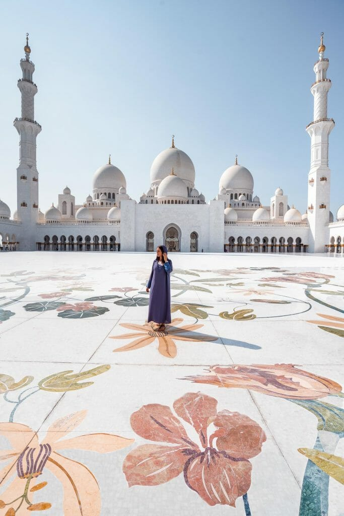 Girl in a blue abaya standing in the middle of Sheikh Zayed Grand Mosque, one of the most Instagrammable places in Abu Dhabi