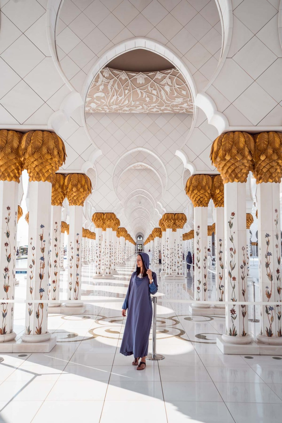 Girl in a blue abaya standing between the gold-white columns in Sheikh Zayed Grand Mosque, Abu Dhabi