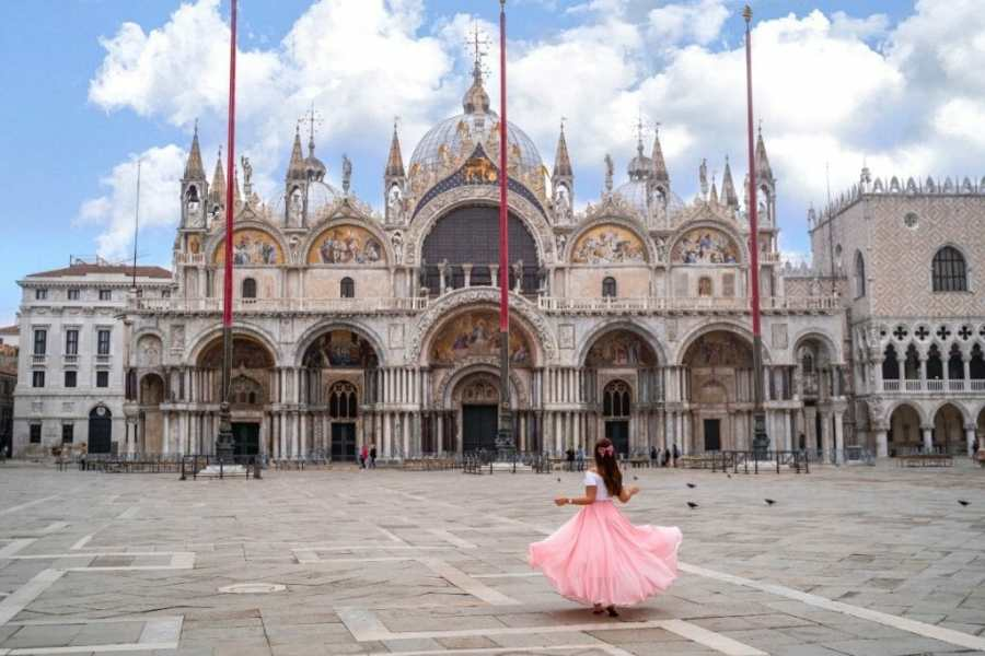 Girl in a pink dress twirling in front of the St. Marks Basilica in Venice, Italy