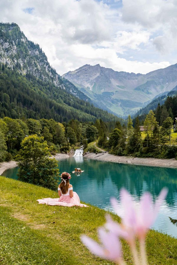 Girl in a pink skirt sitting on the shores of Stausee Steg in Liechtenstein