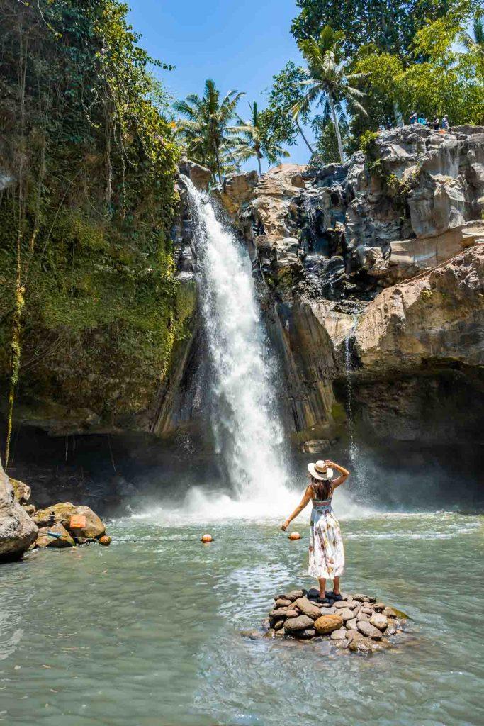 Girl standing on a rock at Tegenungan Waterfall in Bali