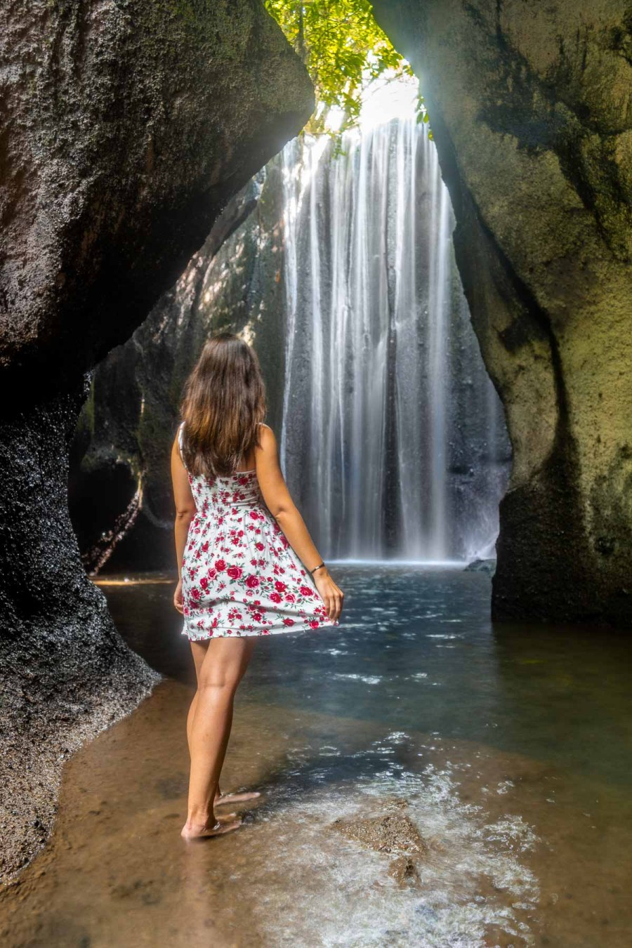 Girl in a red floral dress standing in front of Tukad Cepung Waterfall in Bali