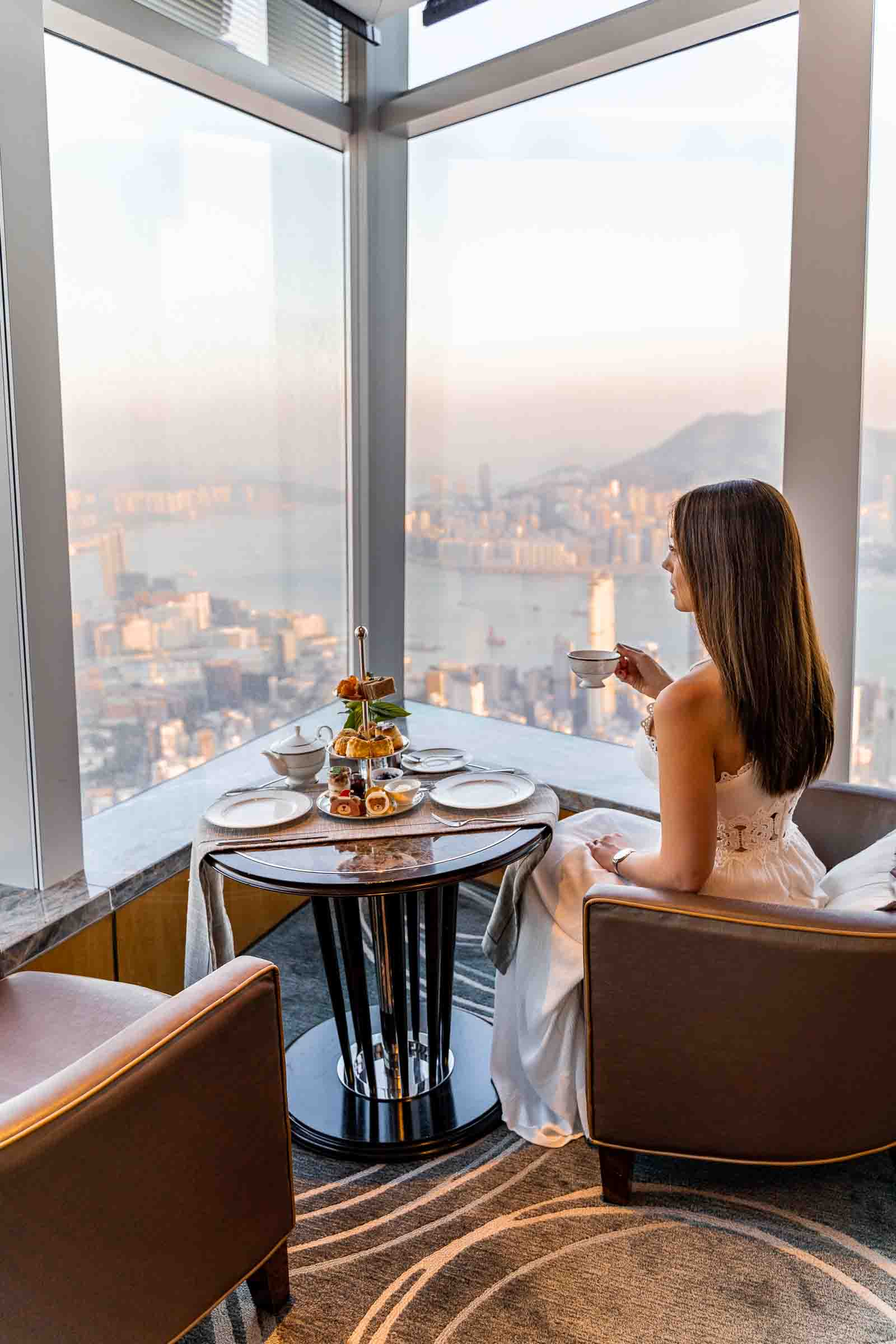 Girl in white dress drinking tea in front of a window with the view of the Hong Kong skyline