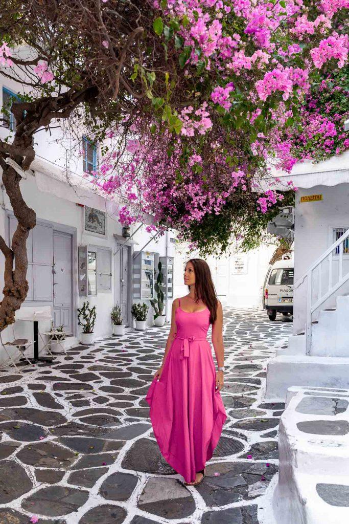 Girl in a pink dress standing under a huge pink bougainvillea tree in Mykonos
