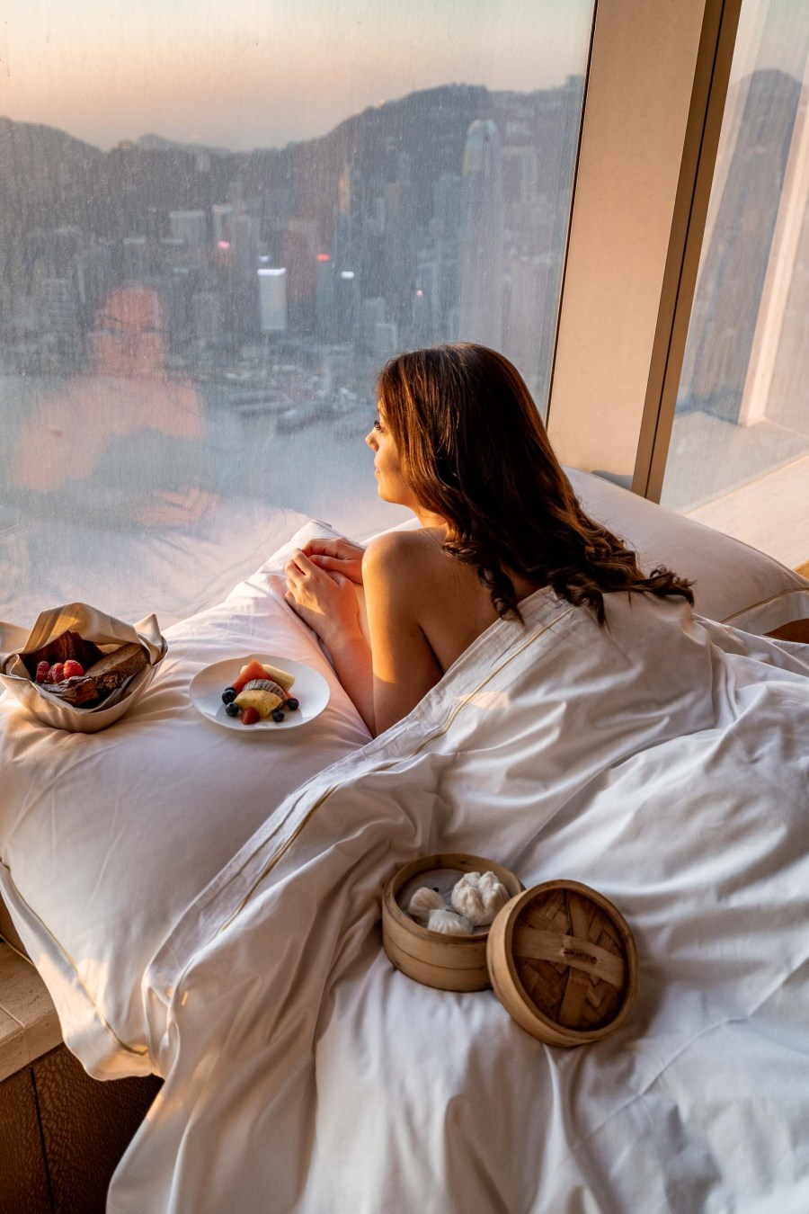 Girl watching the sunrise from the bed